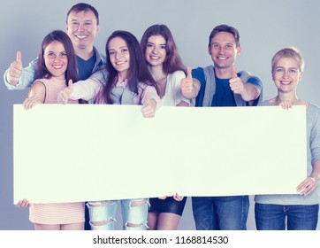Young group of people standing together, holding a blank and showing ok