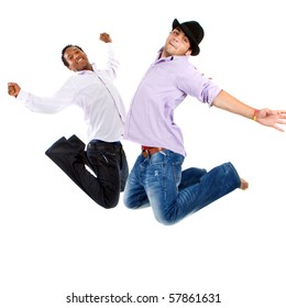 Young group of teenagers with trendy clothes jumping in joy over white background.