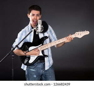 Young guitar player singing into microphone. Dark background