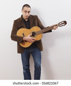 young guitarist good looking and dressing standing on a wall with a guitar on his arms