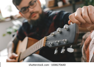 Young guitarist hipster at home with guitar fixing tuning pegs close-up