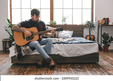 Young guitarist hipster at home with guitar in bedroom sitting on bed's corner