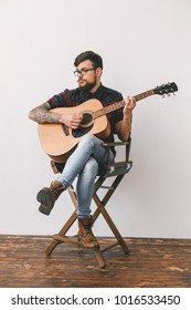 Young guitarist hipster at home with guitar on the chair full-body portrait
