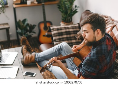 Young guitarist hipster at home playing guitar concentrated
