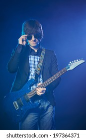 Young guitarist on stage standing in smoke lowering his sunglasses