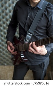 Young guitarist playing on electric guitar. Selective focus.