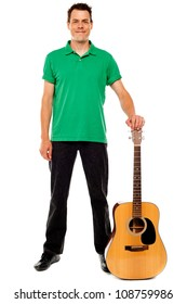 Young guitarist standing with guitar isolated on white background