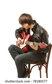 A young guitarist wearing a leather jacket
