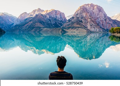 Young guy admiring the morning reflecting view of  turquoise Lake Iskanderkul (Iskander Kul) Fann mountains, Tajikistan, Central Asia