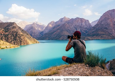 Young guy admiring the view of turquoise Lake Iskanderkul (Iskander Kul) Fann mountains, Tajikistan, Central Asia