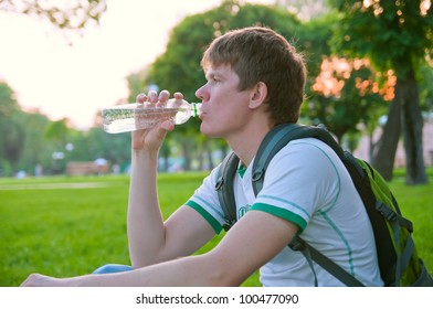 young guy with a backpack drink water from a bottle on the nature