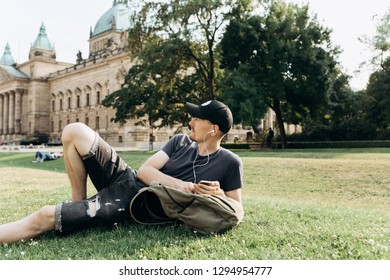A young guy with a backpack or a student lies on the grass and listens to music or a podcast and enjoys.