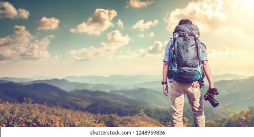 A young guy with a backpack traveler standing on a cliff holding camera and watching White misty mountains. Travel photo lifestyle