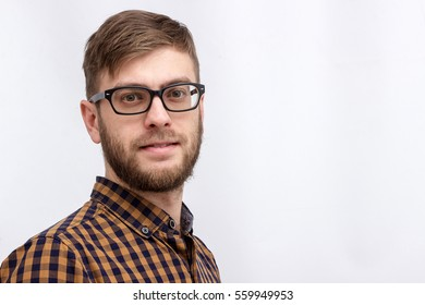 young guy with a beard and glasses in a plaid shirt over a white background