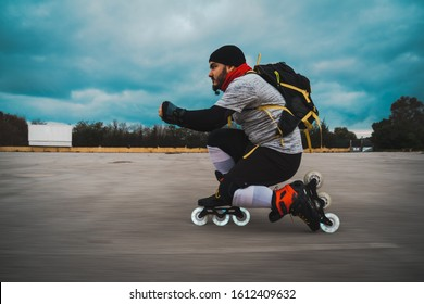 Young guy with a beard, hat and a black backpack skating while is bending the knee in a city parking lot as the sun goes down