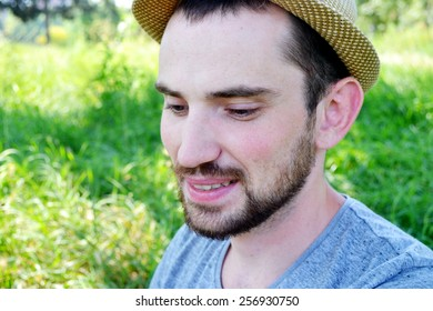 Young guy with beard and in a hat laughing and smiling