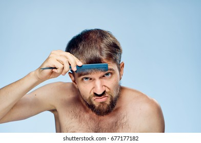 Young guy with a beard on a blue background combing.