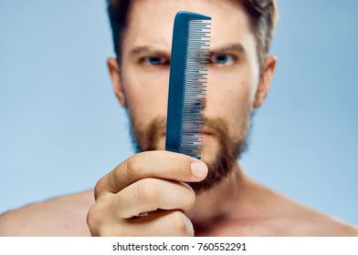 Young guy with a beard on a blue background holds a comb.
