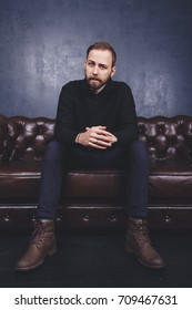 young guy with a beard on the face posing in Studio. sitting on the leather brown sofa. short hair and clean skin. Wallpapers for your desktop. emotional portrait