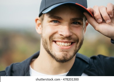 Young guy with beard on his handsome sexy smiling face blue eyes in casual clothes with dark baseball cap on head tipping by hand outdoor