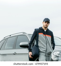 Young guy with beard on his serious face in casual hoody dark blue baseball cap on head and sports bag posing on background of gray car outdoor