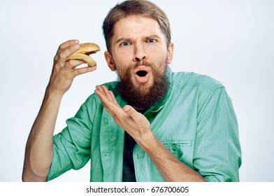 Young guy with a beard on a white isolated background holds a hamburger.