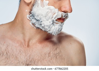 Young guy with beard on white isolated background in shaving foam.