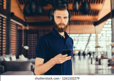 young guy with a beard in a shirt and headphones,Young and smiling man sitting on the roof with mobile phone and listening music (intentional sun glare and vintage color, focus on mobile phone