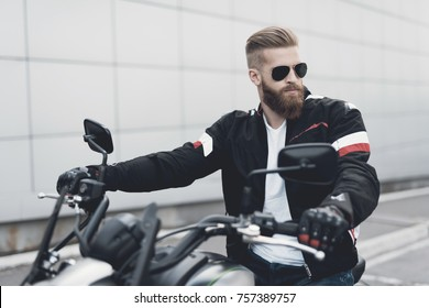 A young guy with a beard sits on his electric motorcycle. He feels confident and is preparing to travel. He wears sunglasses.
