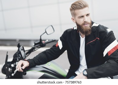 A young guy with a beard sits on his electric motorcycle. He feels confident and is preparing to travel.