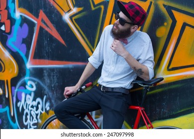 Young guy with beard standing next to a graffiti wall with a bicycle.