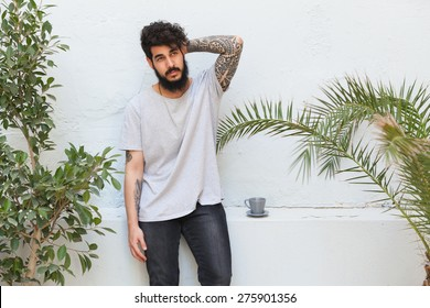 young guy with beard and tattooed arm posing
