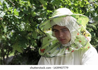 Young guy, beekeeper in beekeeper's protective mask. Young beekeeper bitten by a bee. Pensive, sad, upset beekeeper at the apiary. Work at the apiary