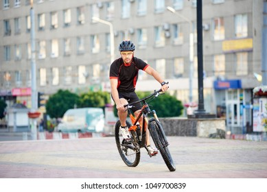 Young guy bicyclist riding on bike in cycling clothes in front of modern city building. Sportsman exercising outdoors, rest after working day. Concept of healthy life