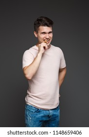 young guy bites a coin bitcoin with his teeth, checking for authenticity, isolated on a gray background.