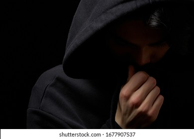 a young guy in a black hoodie on a black background with his face covered.