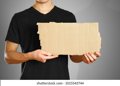 A young guy in a black t-shirt holding a piece of cardboard. Prepared for your text.