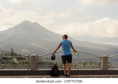 young guy in a blue T-shirt and shorts looks at a volcano on the island of Bali