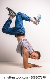 Young guy breakdancing at studio over white background.