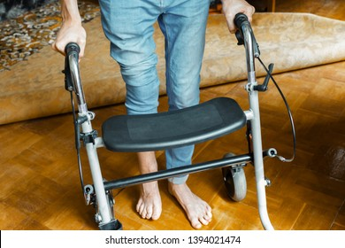 young guy with a broken and deformed leg is standing with a walker on the floor in his room. rehabilitation of victims in hostilities after injuries concept. aftermath of the war and disabled