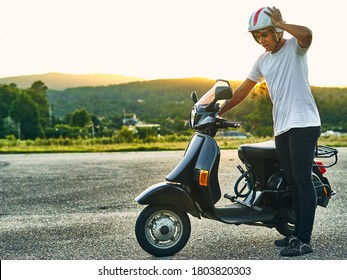 Young guy with broken motorcycle and looking worried and sunset in the background. Dark haired boy wearing white helmet with flag of Italy wearing white t-shirt and black motorcycle with mountains