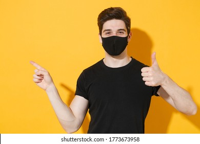 Young guy in casual black t-shirt face mask isolated on yellow background studio. Epidemic pandemic coronavirus 2019-ncov sars covid-19 flu virus concept. Showing thumb up pointing index finger aside