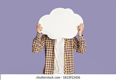 Young guy in casual clothes closing his face with speech bubble on lilac background, space for design