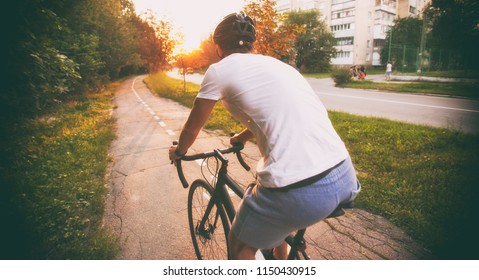 The young guy in casual clothes is cycling on the road in the evening city