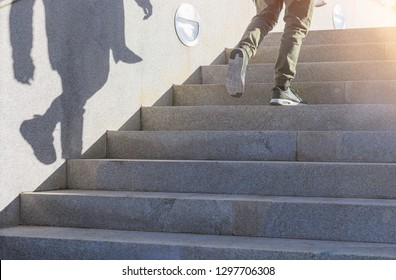 Young guy in casual clothing is walking up an outdoor stone stairs with his shadow shown on the wall, climbing / growing concept, view from downstairs