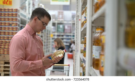 young guy chooses a sunflower oil in a store or supermarket