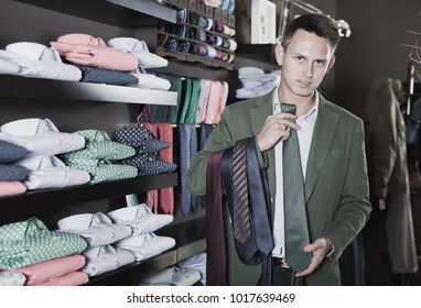 Young guy choosing new tie in male cloths store