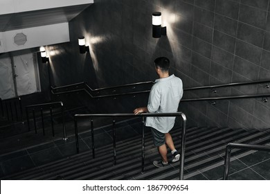 A young guy comes down the stairs, an underground passage. Subway, stairs down