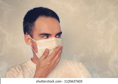 A young guy covers his nose in a mask. Bad smell the stench, the Concept of quarantine. smoke blanketing. the concept of air pollution and the environment. toxic