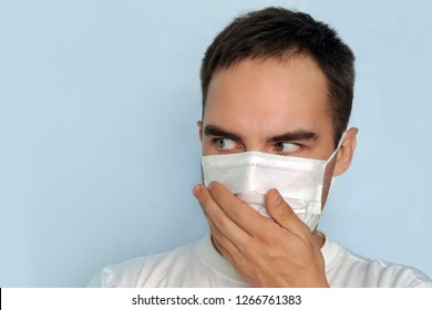 A young guy covers his nose in a mask. Bad smell the stench, the Concept of quarantine.